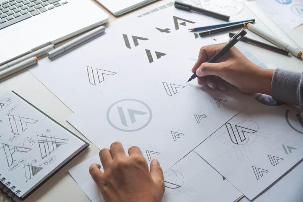 A designer sketching a logo onto paper.