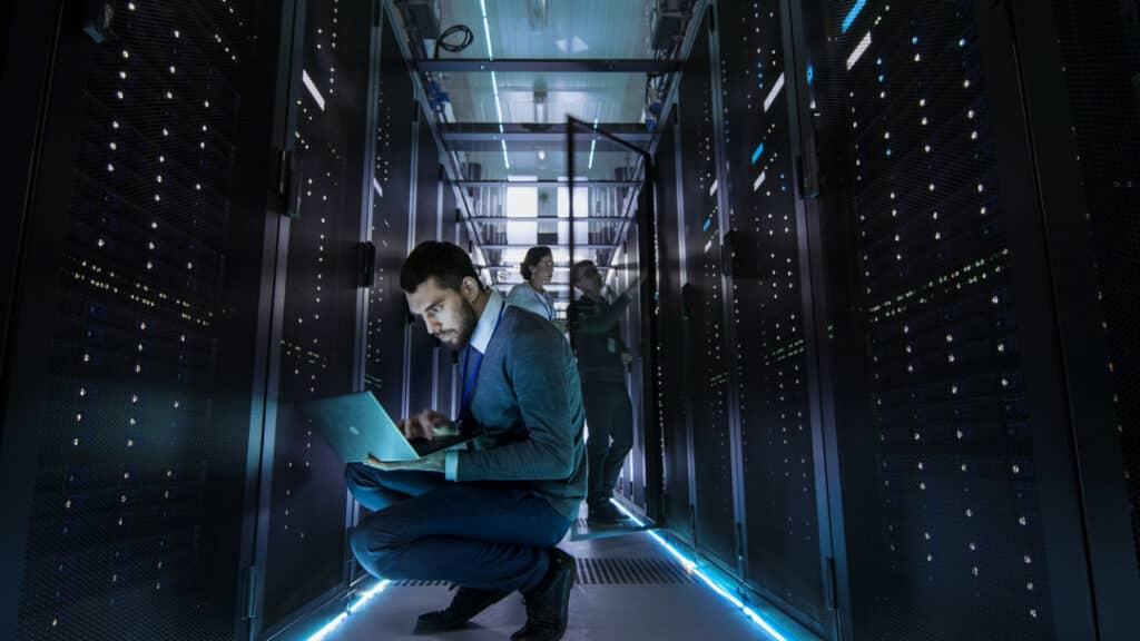 Des informaticiens dans une salle de serveurs effectuant la maintenance.